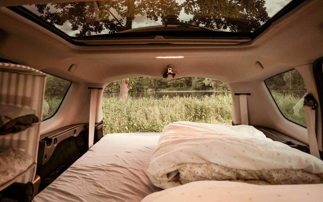 Von Innen besticht der Mini Camper mit einem Panorama Fenster und Ausblick aus dem offenen Kofferraum