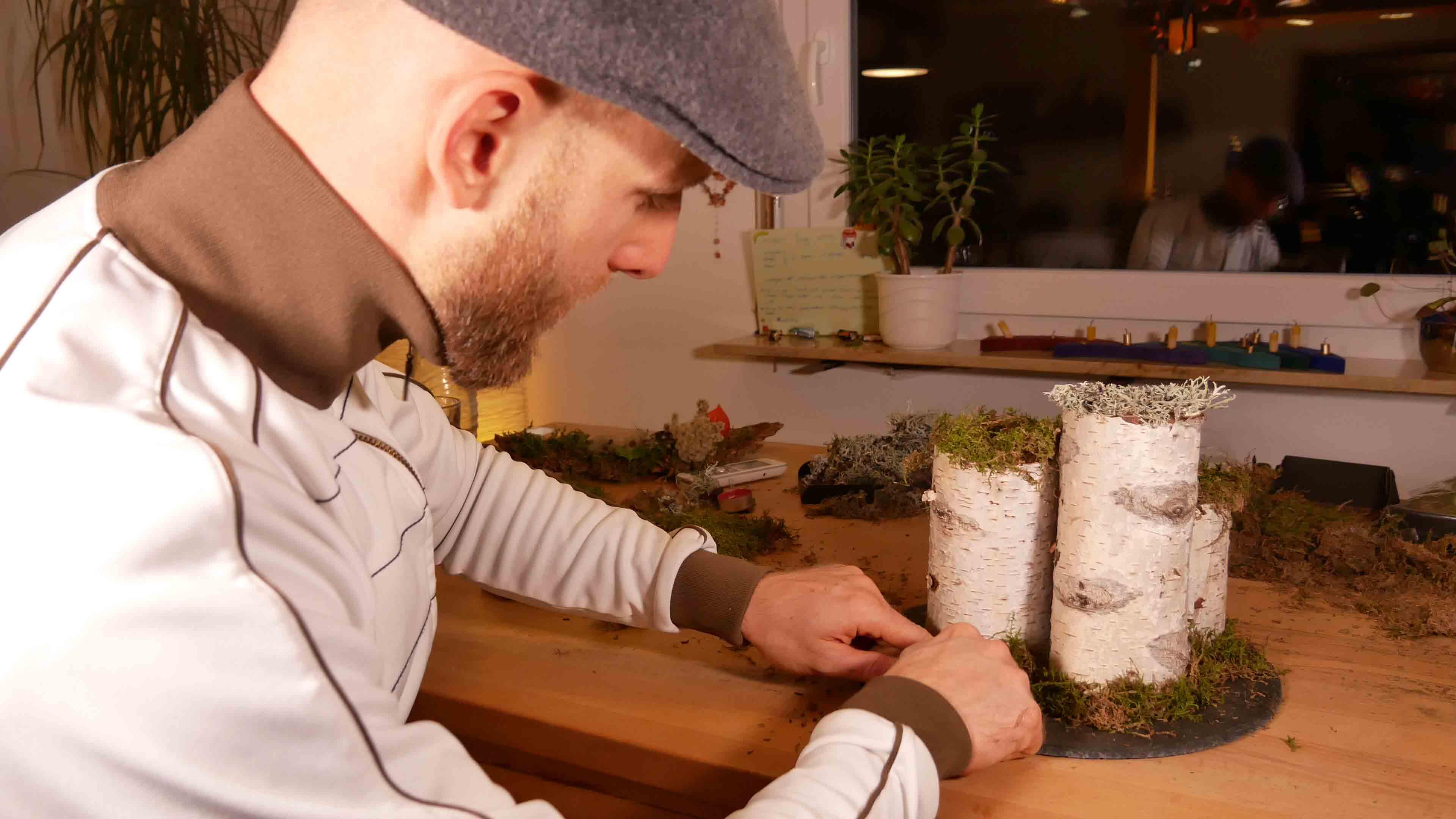 Das selber gemachte Adventsgesteck wird auf eine runde Schieferplatte gestellt