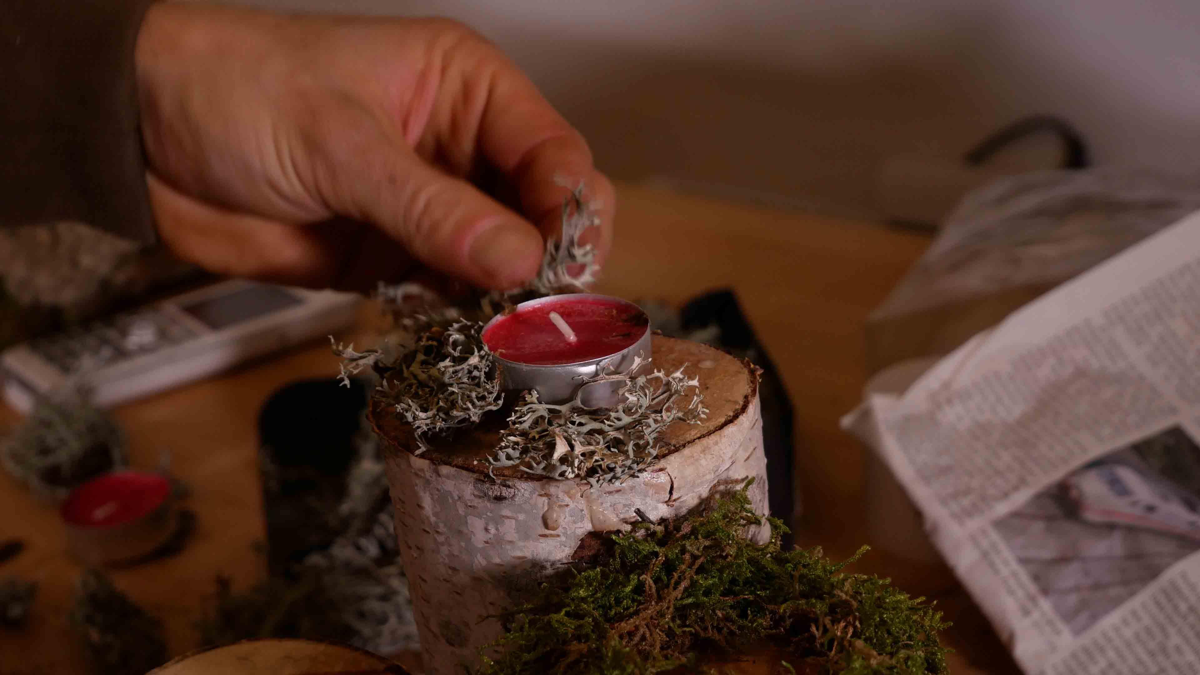 Die Birkenstämme werden zum Dekorieren für das selber gemachte Adventsgesteck mit Sprühkleber eingespüht