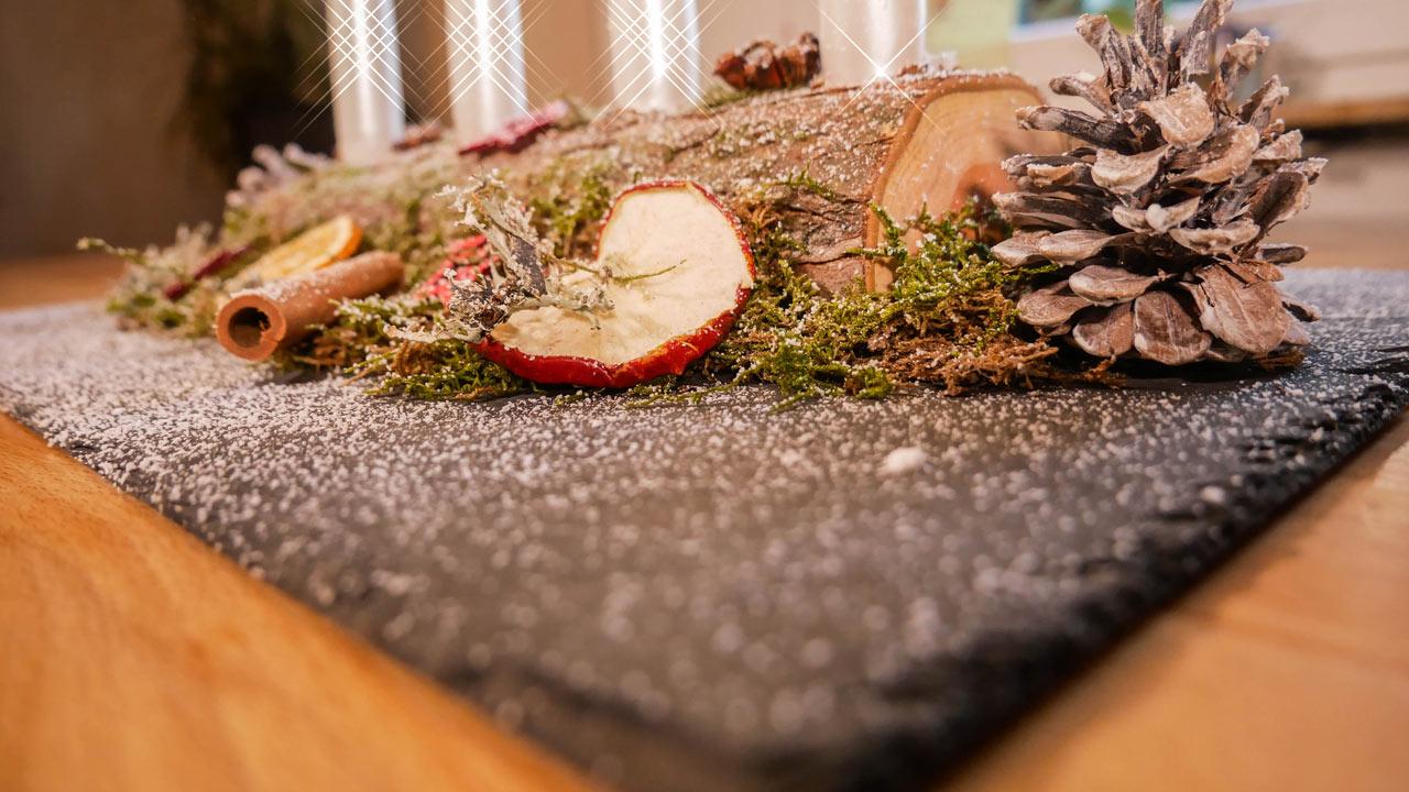 Das selbst gemachte Adventsgesteck wird auf einer Schieferplatte angerichtet