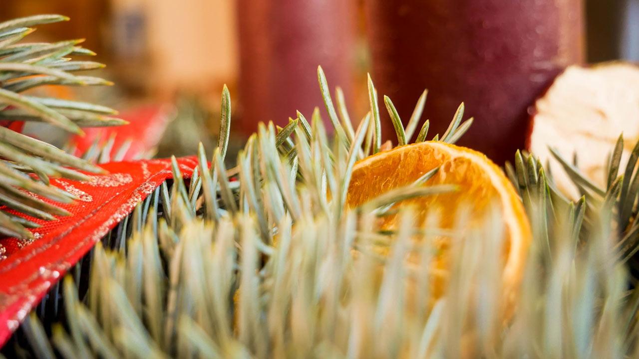 Der selber gemachte Adventskranz wird mit getrockneten Orangenscheiben dekoriert