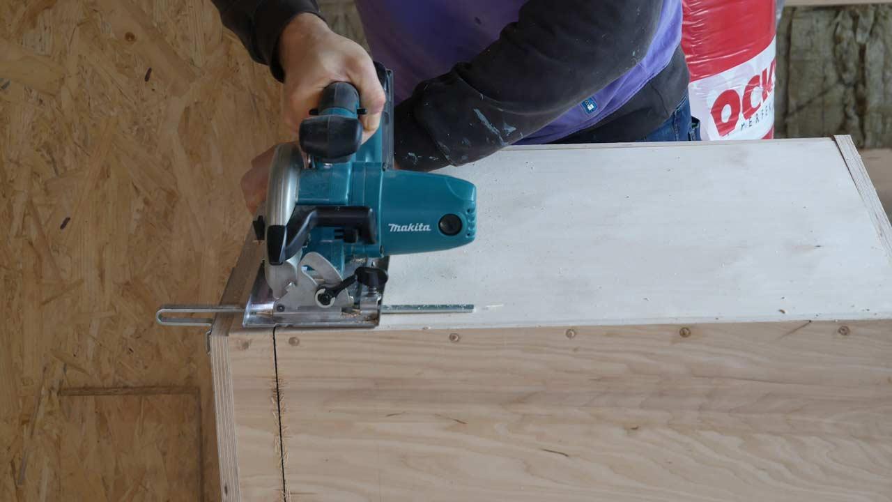 Der spätere Deckel der selbstgebauten Holzkiste wird mit einer Handkreissäge abgesägt