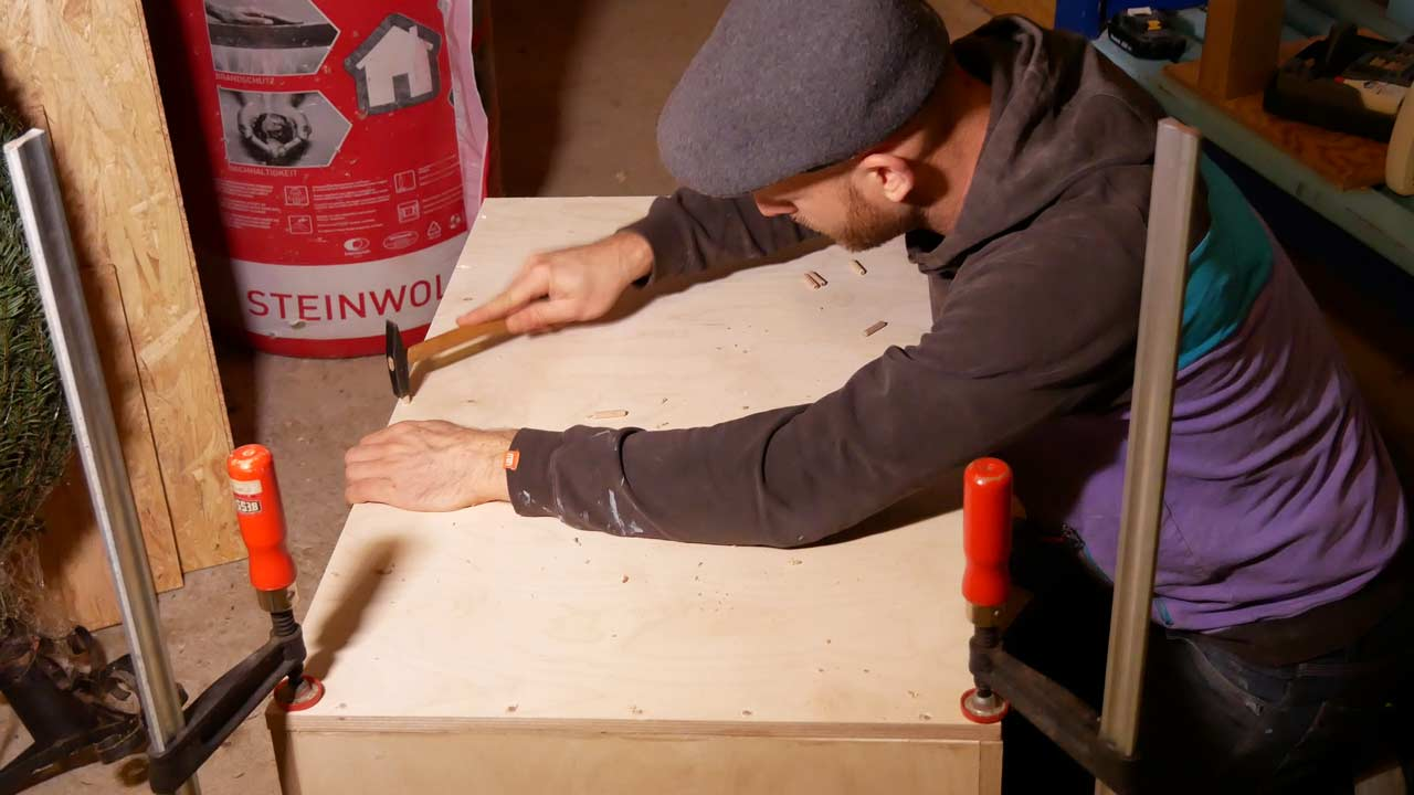 Die Bretter der selbstgebauten Holzkiste werden mit Dübel miteinander verbunden