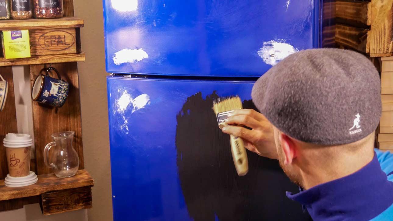 Mit einem Lackpinsel wird der Tafellack auf den Kühlschrank aufgetragen