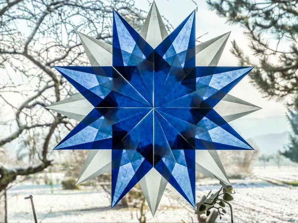 Der fertige Weihnachtsstern aus Transparentpapier wird an den Fenster gehängt